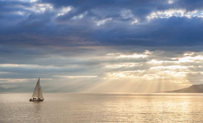 Small sailboat sailing on the lake Leman (Switzerland) at sunset