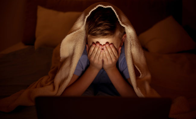 Terrified little boy spending evening at home