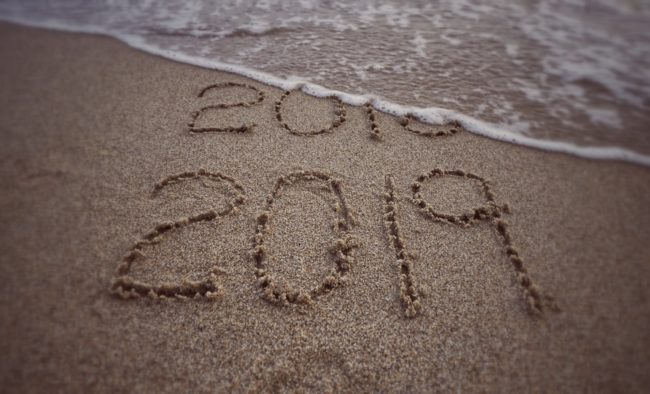 New Year concept - '2019' formed on background of beach sand. With blurred vintage styled background.
