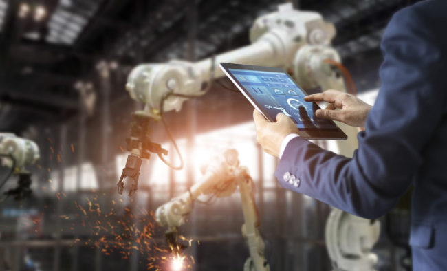 Industrial engineer manager using tablet control automation robot arms machine in intelligent on monitoring. Welding robotics and digital manufacturing operation. Industry 4.0 concept