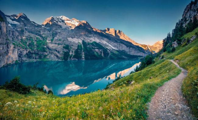 Spectacular summer view of unique Oeschinensee Lake. Majestic morning scene of Swiss Alps with Bluemlisalp mountain on background, Kandersteg village location, Switzerland, Europe.
